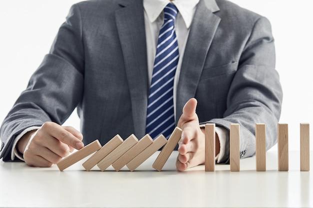 Uomo d'affari in un vestito che protegge i blocchi di legno dalla caduta in un effetto domino