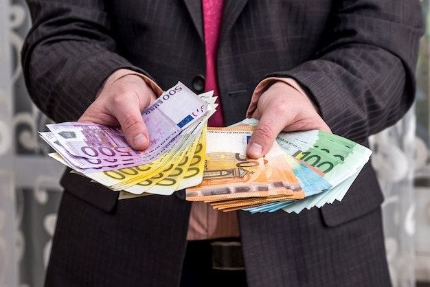 Businessman in suit showing earnings, euro banknotes