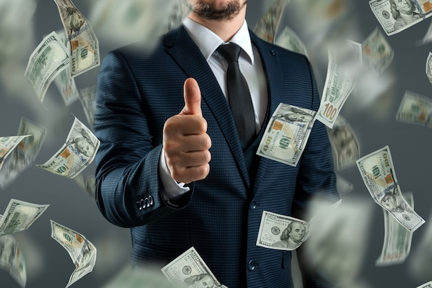 A businessman in a suit shows thumbs up against the background of falling dollars. the concept of investments, dividends, interest, bank deposits.