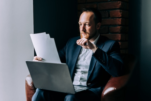 A businessman in a suit sits in an armchair with a laptop and analyzes a financial report.