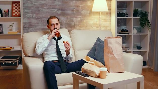 Uomo d'affari in abito seduto sul divano a mangiare un hamburger, bere birra e guardare la tv.