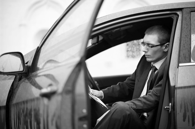Businessman in a suit on the street in a car