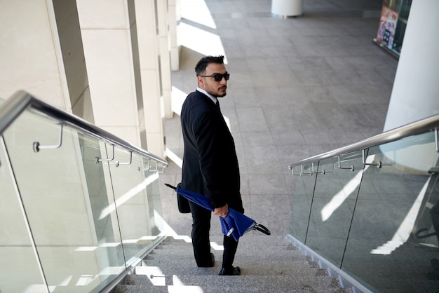 Businessman in suit and sunglasses walking down staircase and looking around at camera