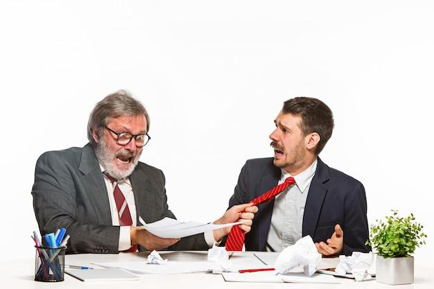 Uomo d'affari in un vestito che prende un dono all'ufficio sullo studio bianco