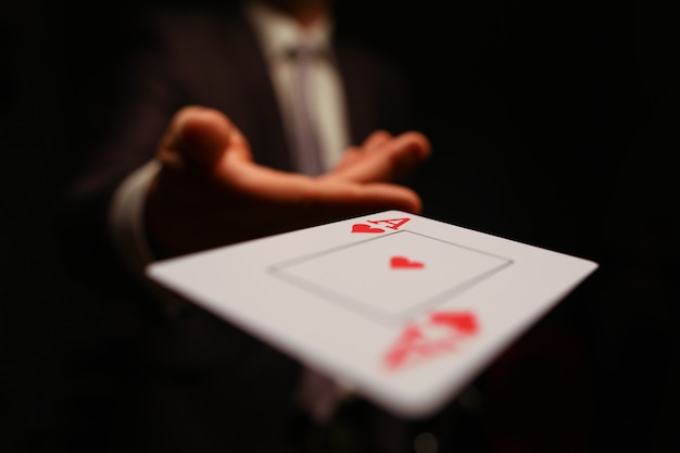 Businessman in suit throws his hand playing card ace