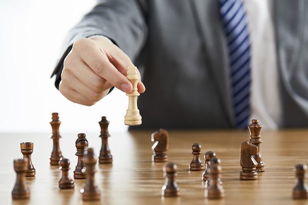 Businessman in a suit using his white king chess piece among dark chess pieces on a table