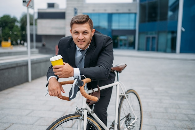 Businessman in suit with briefcase and bicycle in downtown. business person riding on eco transport on city street