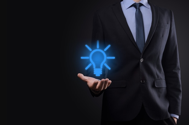 Businessman in a suit with a light bulb in his hands. holds a glowing idea icon in his hand. with a place for text.