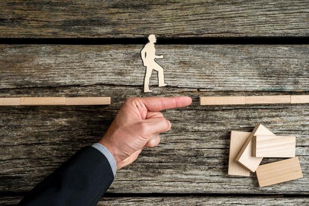 Бизнесмен, поддерживающий бумагу, вырезанную из человека, идущего к успеху