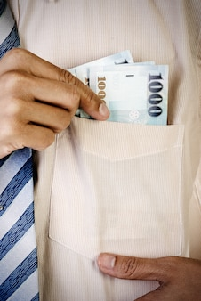 Бизнесмен берет деньги из кармана формы тайваньского счета.