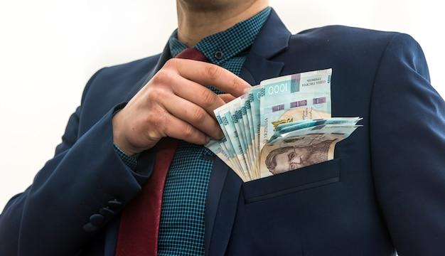 ビジネスマンは賄賂としてウクライナのお金のパックを取り、ジャケットの彼のポケットに隠れます。腐敗とトリック。 uah。 1000枚の新しい紙幣