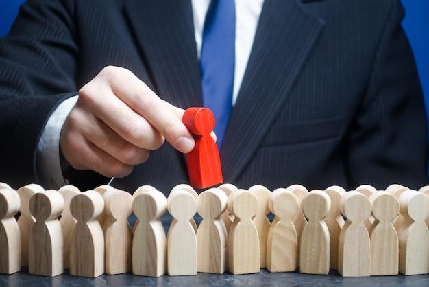 Бизнесмен вынимает красного человека из толпы людей.