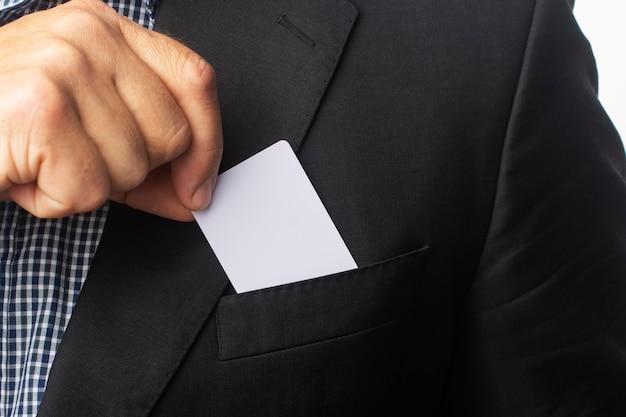 Бизнесмен достает белую визитку из кармана пиджака.