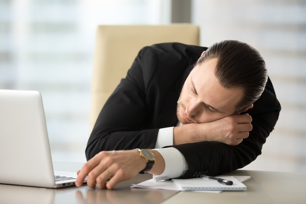 Businessman takes break and dozing in office