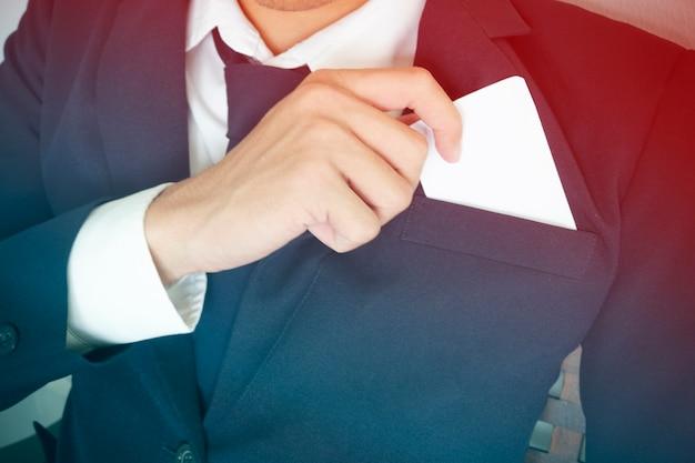 Бизнесмен вынимает визитную карточку из кармана костюма, копирует пространство
