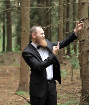 松林で自分撮りをしているビジネスマン