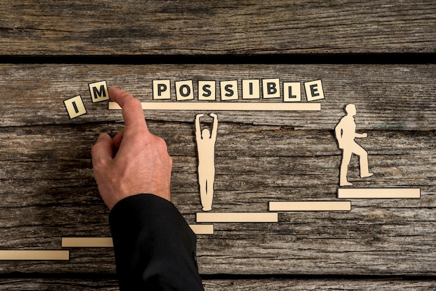 Businessman taking away letters im from the word impossible changing it into possible with silhouette cutout helping and a cutout of a climbing man on cracked old wooden desk. teamwork concept.