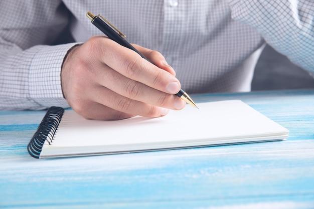 Бизнесмен делает заметки в записной книжке.