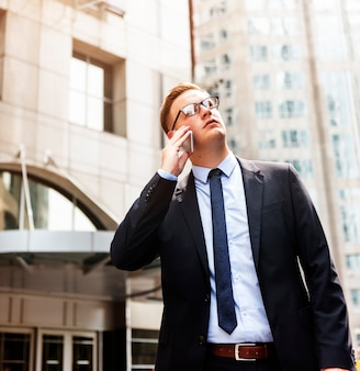 ビジネスマンtalkin電話屋外思考の概念
