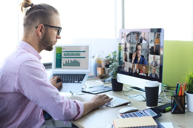 Businessman talking to his colleagues in video conference. multiethnic business team working from office using computer pc, discussing financial report of their company.