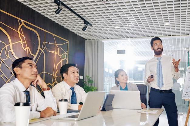 Бизнесмен разговаривает перед коллегами