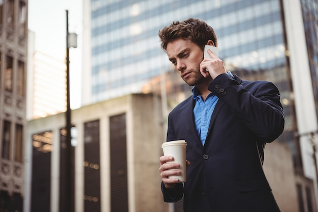 Businessman talking on mobile phone and holding coffee