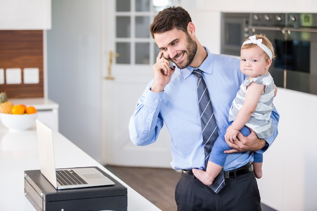 Businessman talking on mobile phone while carrying daughter