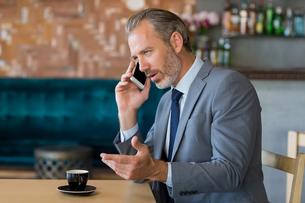 Businessman talking on mobile phone while having a cup of tea
