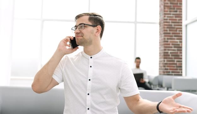 ロビーで携帯電話で話しているビジネスマン
