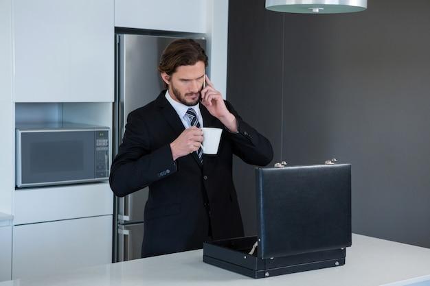 Бизнесмен разговаривает по мобильному телефону на кухне