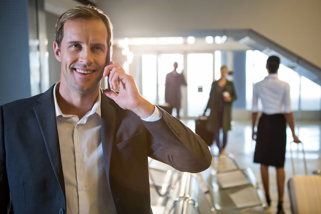 Бизнесмен разговаривает по мобильному телефону в зоне ожидания