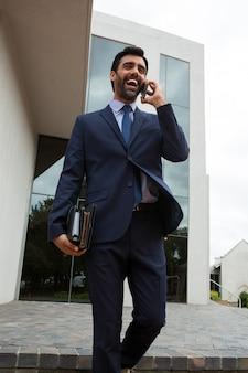オフィスビルの近くで携帯電話で話しているビジネスマン