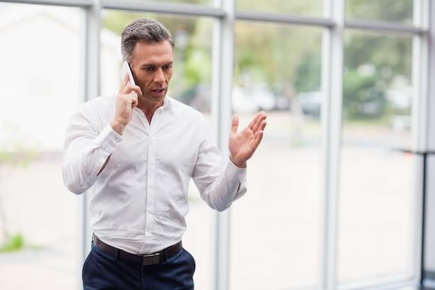Бизнесмен разговаривает по мобильному телефону