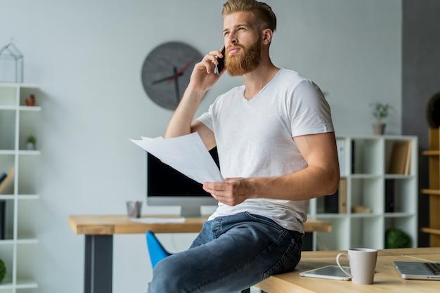 オフィスに座って携帯電話で話しているビジネスマン。