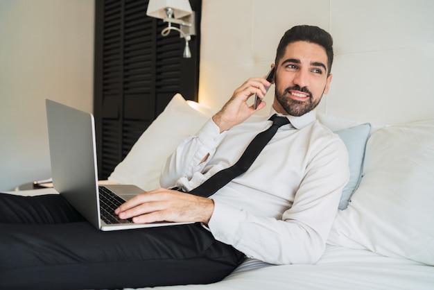 ホテルの部屋で電話で話しているビジネスマン。
