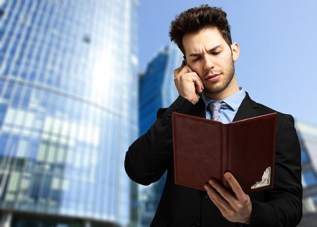 クライアントと電話で話し、議題を確認するビジネスマン