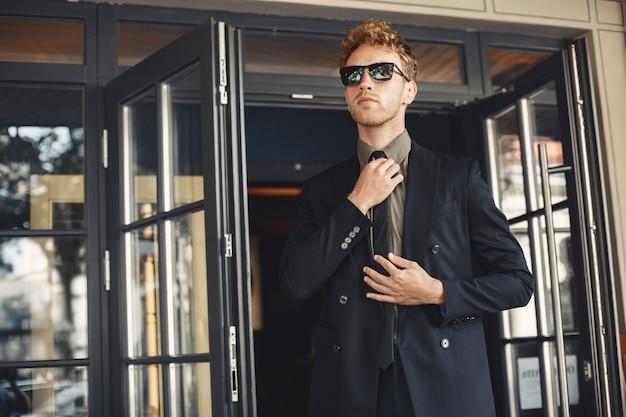 Бизнесмен разговаривает по телефону и держит в руках папку. человек в солнечных очках.