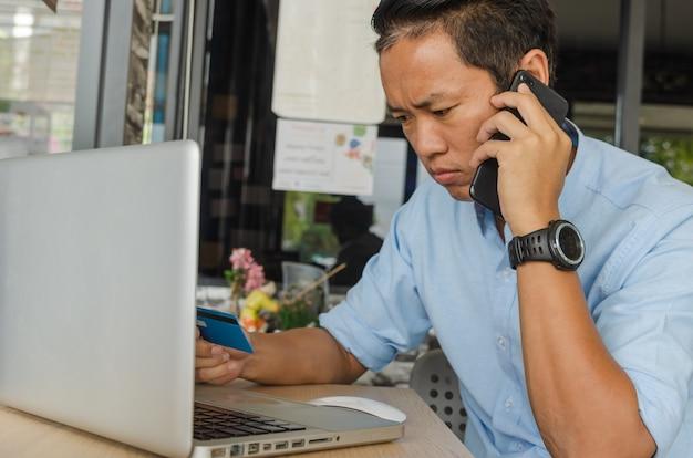 Бизнесмен разговаривает по телефону и смотрит на кредитные карты, проверяя расходы по долгу