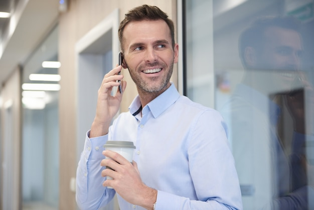 Бизнесмен разговаривает по телефону на работе