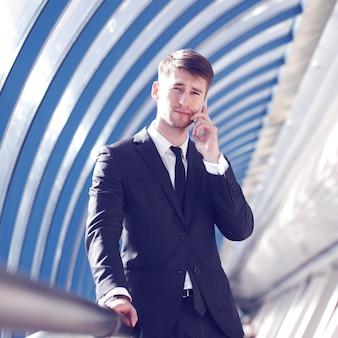 Бизнесмен разговаривает по телефону в современном здании