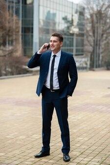 Бизнесмен разговаривает по телефону на улице
