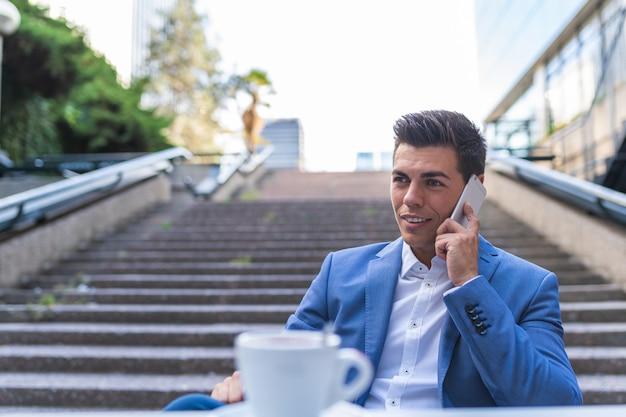 カフェに座って電話で話しているビジネスマン。屋外で携帯電話を使用している若い男。ビジネスコンセプト。