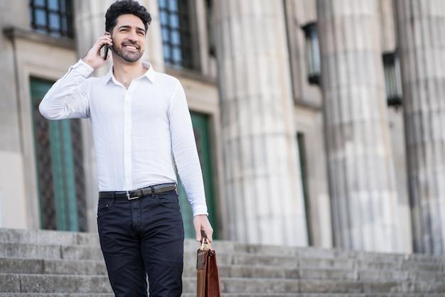 屋外の階段に立って電話で話しているビジネスマン。ビジネスコンセプト。