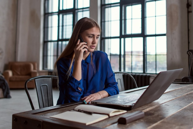 スタイリッシュでモダンなオフィスで彼女の机に座ってラップトップで作業しながら電話で話しているビジネスマン。