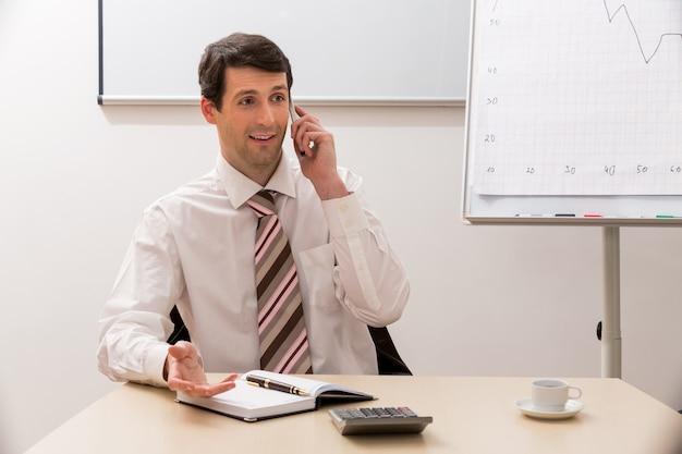 電話でビジネスパートナーの男性と電話で話しているビジネスマン