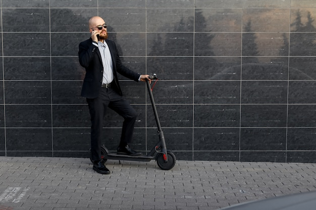 Businessman talking on the phone, next to the electric scooter