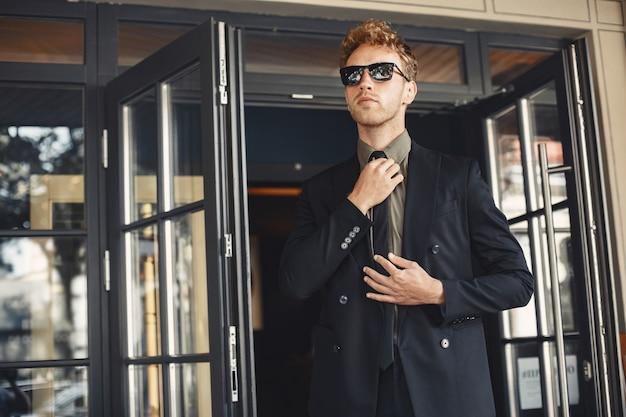 Uomo d'affari parlando al telefono e tenendo una cartella nelle sue mani. uomo in occhiali da sole.