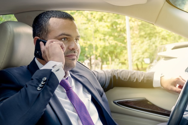 Businessman talking on the phone while driving in a traffic jam portrait of a driver