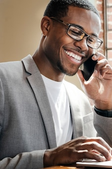 Businessman talking on a phone while using a laptop