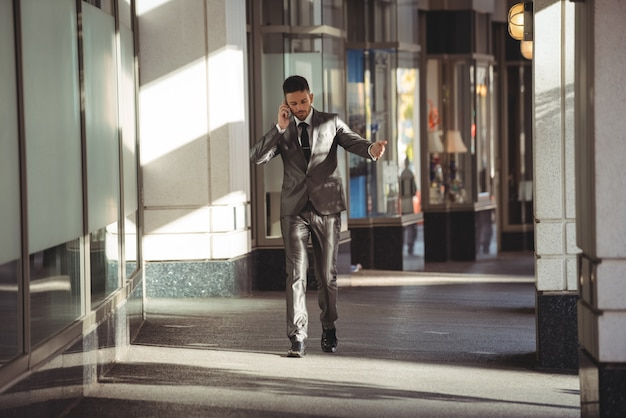 Businessman talking on the phone while walking